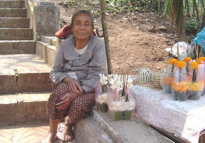 old lady selling flowers and caged birds