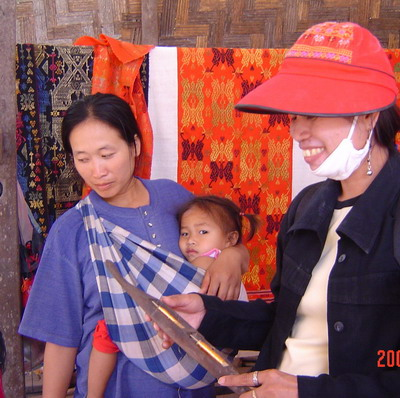 Ann at village looking at weaving